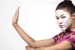 Pretty Geisha woman. A studio view of a pretty woman wearing Geisha make up and purple dress holds her hands in a thai chi position.  White background Royalty Free Stock Photos