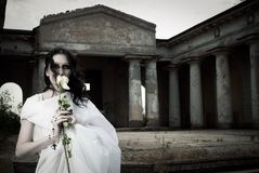 Pretty ghost. Pretty gothic girl with a  flower posing on a cemetery Royalty Free Stock Photos