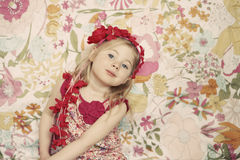 Pretty girl. Pretty little girl wearing flower headband looking into camera in front of floral background Stock Photography