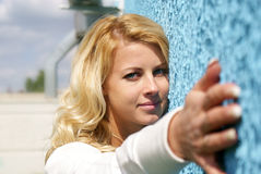 Pretty girl. Blond young girl with blue wall Royalty Free Stock Photos
