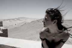 Pretty girl. Pretty brunette is sitting on the wind in desert Royalty Free Stock Image