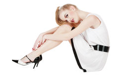 Pretty girl. Beautiful blond girl in stylish dress and stilettos sitting on white background and smiling Royalty Free Stock Images