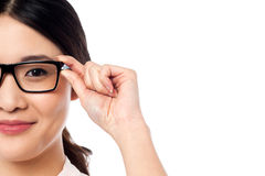 Pretty girl adjusting her spectacles Royalty Free Stock Image