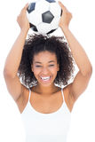 Pretty girl with afro hairstyle smiling at camera holding football Stock Photography