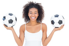 Pretty girl with afro hairstyle smiling at camera holding footballs Stock Photos