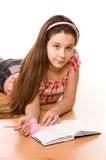 Pretty girl in the age of eleven making notes. On diary on the floor on white Royalty Free Stock Photography