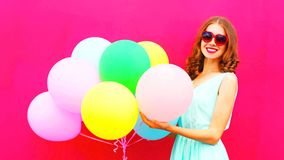 Pretty girl with an air colorful balloons having fun in summer. Over pink background Stock Photos