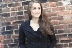 Pretty Girl alone near grunge wall Stock Photo