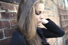 Pretty Girl alone near grunge wall Stock Images