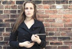 Pretty Girl alone near grunge wall Royalty Free Stock Photography