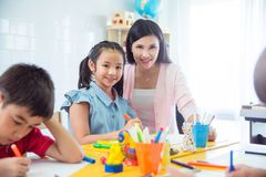 Free Pretty Girl And Teacher Smiling In Classroom Stock Photography - 115855672