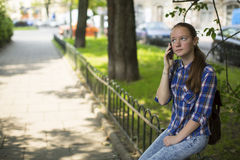 Pretty girl anxiously talking on the cell phone while sitting outdoors. Stock Photography