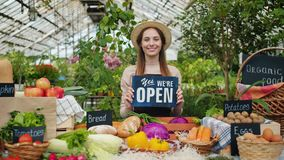Pretty girl in apron and hat holding open sign in organic food market smiling. Looking at camera standing near table with fruit and vegetables. People and stock video