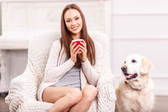 Pretty girl in the armchair with her pet around Stock Images