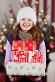 Pretty girl with an armful of Christmas gifts Royalty Free Stock Images
