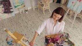 Portrait of a talented girl artist in the studio. Pretty girl artist paints on canvas painting on the easel. Art, creativity, hobby, job and creative occupation stock footage