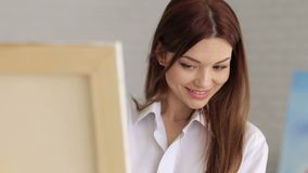A young girl in a white shirt draws on canvas in the studio for drawing.Art stock footage