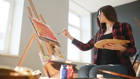 Pretty Pretty Girl artist paints on canvas painting on the easel. Studio black background. Long hair, brunette.  stock footage