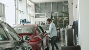 Pretty girl asks the boyfriend to buy her a car in car showroom. Swarthy guy is smiling and nods affirmatively. Happy girl take him by head and sit down on stock video