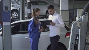 Pretty girl auto mechanic taking datas about car and signed taking key and shaking hand of young handsome man in car stock footage