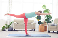 Pretty girl balancing and stretching while standing on one leg Royalty Free Stock Image