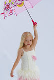 Pretty girl in ballerina dress. Adorable little girl with long blond hair wears a white ballet frock whilst dancing with an umbrella held above her head Royalty Free Stock Photo