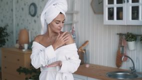 Pretty girl in bathrobe, with towel on her head applies cream to body, slow motion stock video