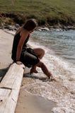 Pretty girl on the beach. Pretty girl sitting on a log on the beach Stock Photos