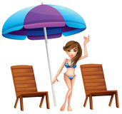 A pretty girl at the beach near the wooden chairs Royalty Free Stock Images