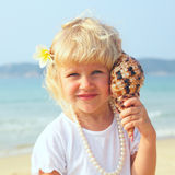 Pretty girl on the beach with seashell Royalty Free Stock Photography
