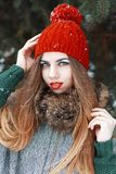 Pretty girl with beautiful blue eyes in a red hat and coat stand. Ing near spruce Stock Photo
