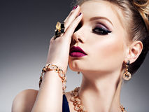 Pretty girl with beautiful face bright make-up and gold jewelry. Posing at studio royalty free stock image
