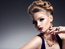 Pretty girl with beautiful hairstyle  and gold jewelry, bright m Royalty Free Stock Photography