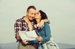 Pretty girl kissing happy man with closed eyes royalty free stock image