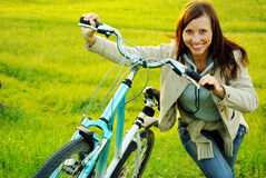 Pretty girl and bicycle. Pretty girl standing with a bicycle on the meadow Royalty Free Stock Photography