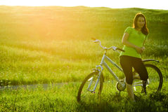 Pretty girl and bicycle. Pretty girl standing with a bicycle on the meadow Stock Photos