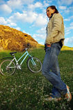 Pretty girl and bicycle. Pretty girl standing with a bicycle on the meadow Royalty Free Stock Photos