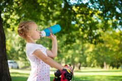 Pretty girl with bicycle drinks water in summer park. Little pretty girl with bicycle drinks water in summer park Stock Photo