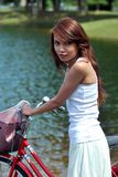Pretty girl with bicycle at the park Royalty Free Stock Photo
