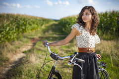 Pretty girl with bike on path Stock Images