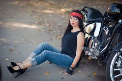 Pretty girl biker or cute woman with stylish, long hair wearing jeans sitting on floor at motorcycle. Pretty girl biker or cute woman with stylish, long hair and stock image