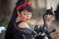 Pretty girl biker or cute woman with stylish, long hair wearing jeans sitting on floor at motorcycle. Pretty girl biker or cute woman with stylish, long hair and stock photo