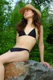 Pretty girl in bikini outdoor. Beautiful young woman in black bikini sitting on a rock outdoors summer scenic royalty free stock image