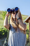 Pretty girl with binoculars looking at the horizon Stock Photos