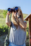 Pretty girl with binoculars looking at the horizon Royalty Free Stock Image