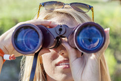 Pretty girl with binoculars looking at the horizon Stock Images