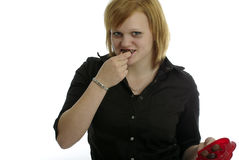 Pretty Girl bites into a chocolate Royalty Free Stock Images