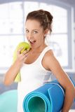 Pretty girl biting apple after workout Stock Image