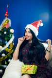 Pretty girl biting mandarin beside Christmas tree stock images