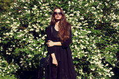 Pretty girl in black clothes outdoors Stock Photos